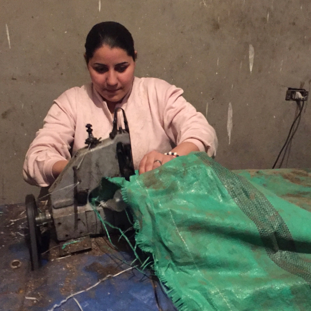 Samia* bought an industrial sewing machine and sews new garbage bags from the torn pieces of old ones.  When she sewed them by hand, she could only make 10 in a day. Now she can produce 50!