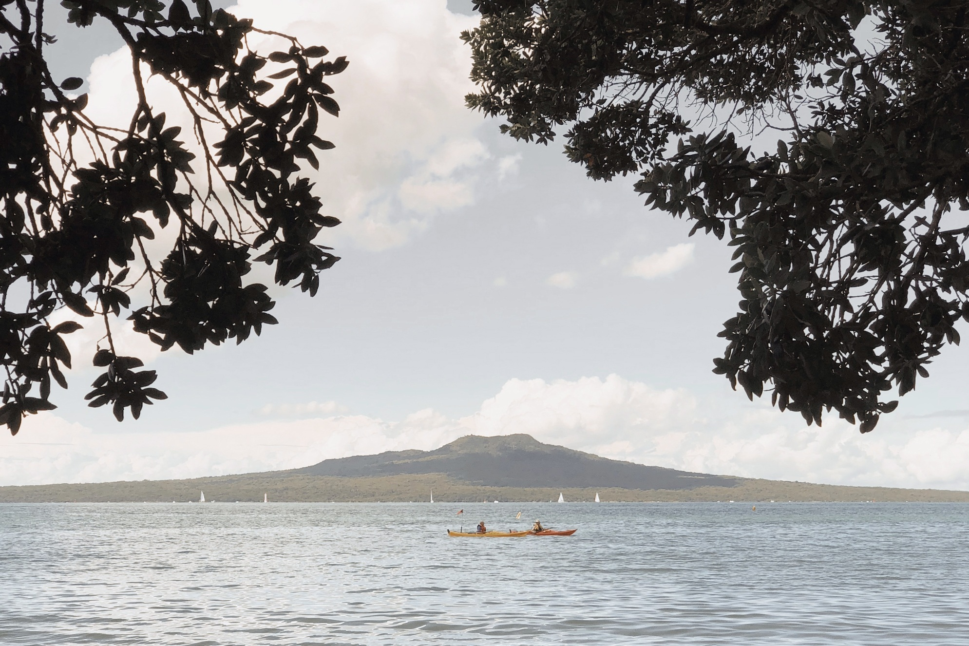 Takapuna - TravelAuckland, New ZealandAlong the historic lava beach trail, two pōhutukawa trees perfectly frame a mesmerising view of the iconic Rangitoto Island across the Hauraki Gulf. Paddle board or kayak at the beach or choose to relax by Lake Pupuke, Auckland's only fresh water lake. Stroll the Sunday markets, take in a live show and enjoy the ever-welcoming hospitality.