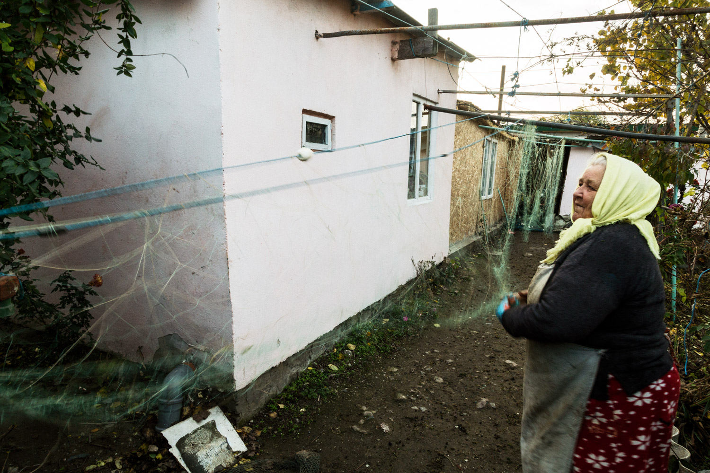 Sulina, Romania,November 2017. A woman working on a fishing net in her backyard.