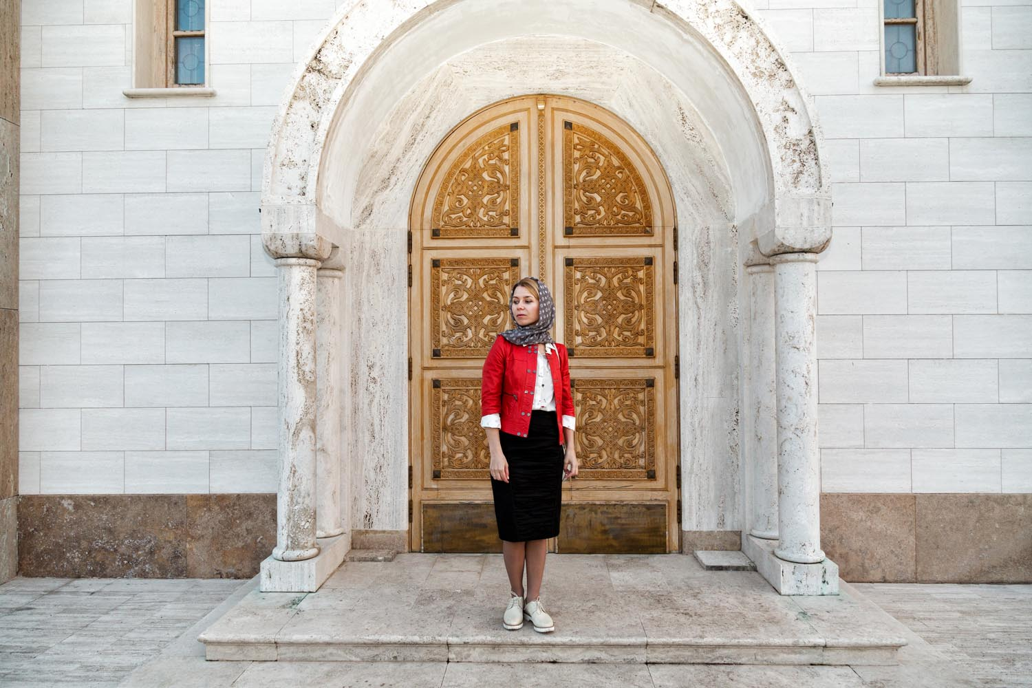 Rome, Italy, Apr 2018.  Saint Catherine Church. Aleksandra, a Ukrainian believer, in front of one of the two lateral doors of the church.