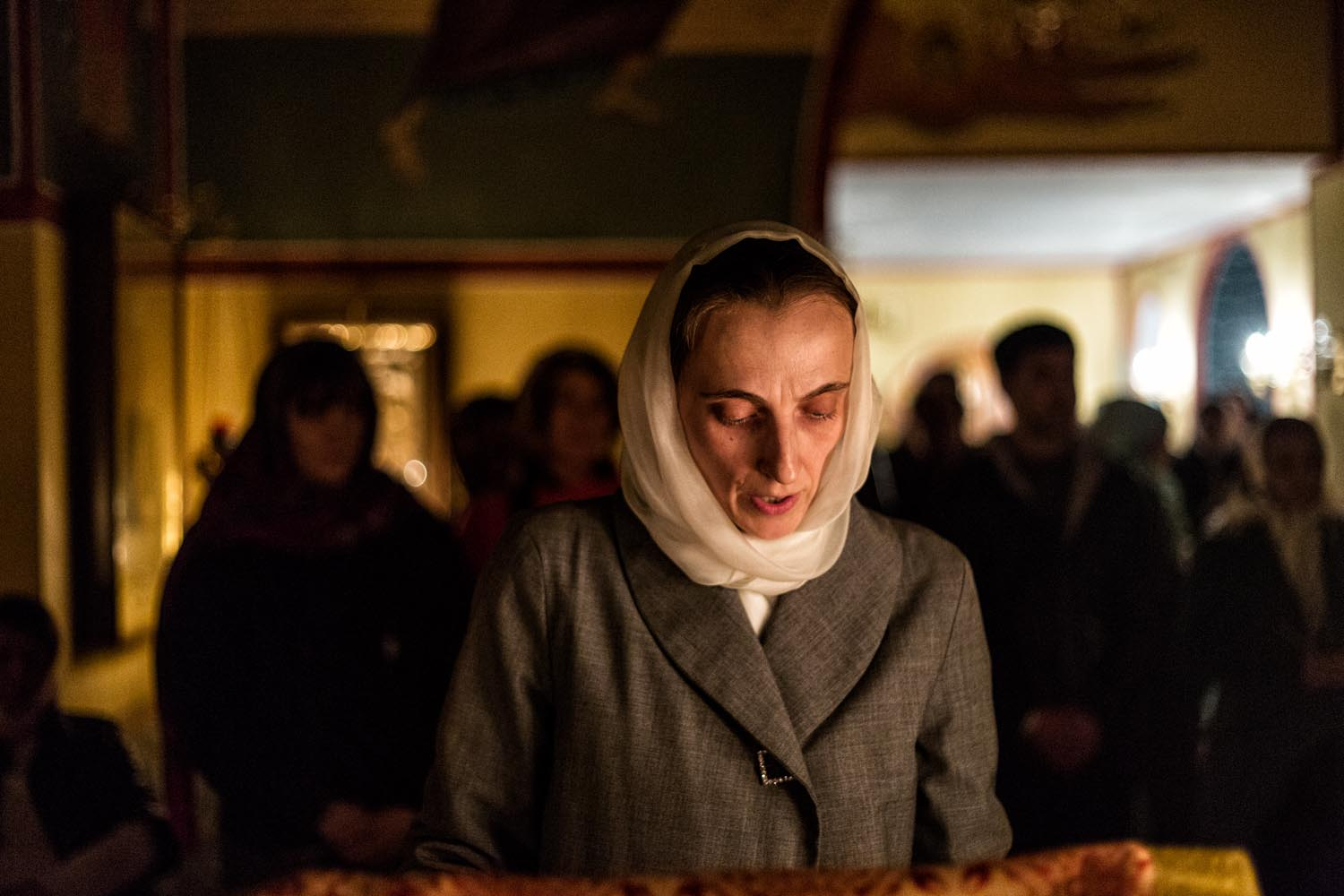 Rome, Italy, Apr 2018.  Saint Chaterine Church. A russian orthodox believer, Maryia, reads the Acts of the Apostle before the divine liturgy which will start after midnight. Behind her, the other believers are praying.