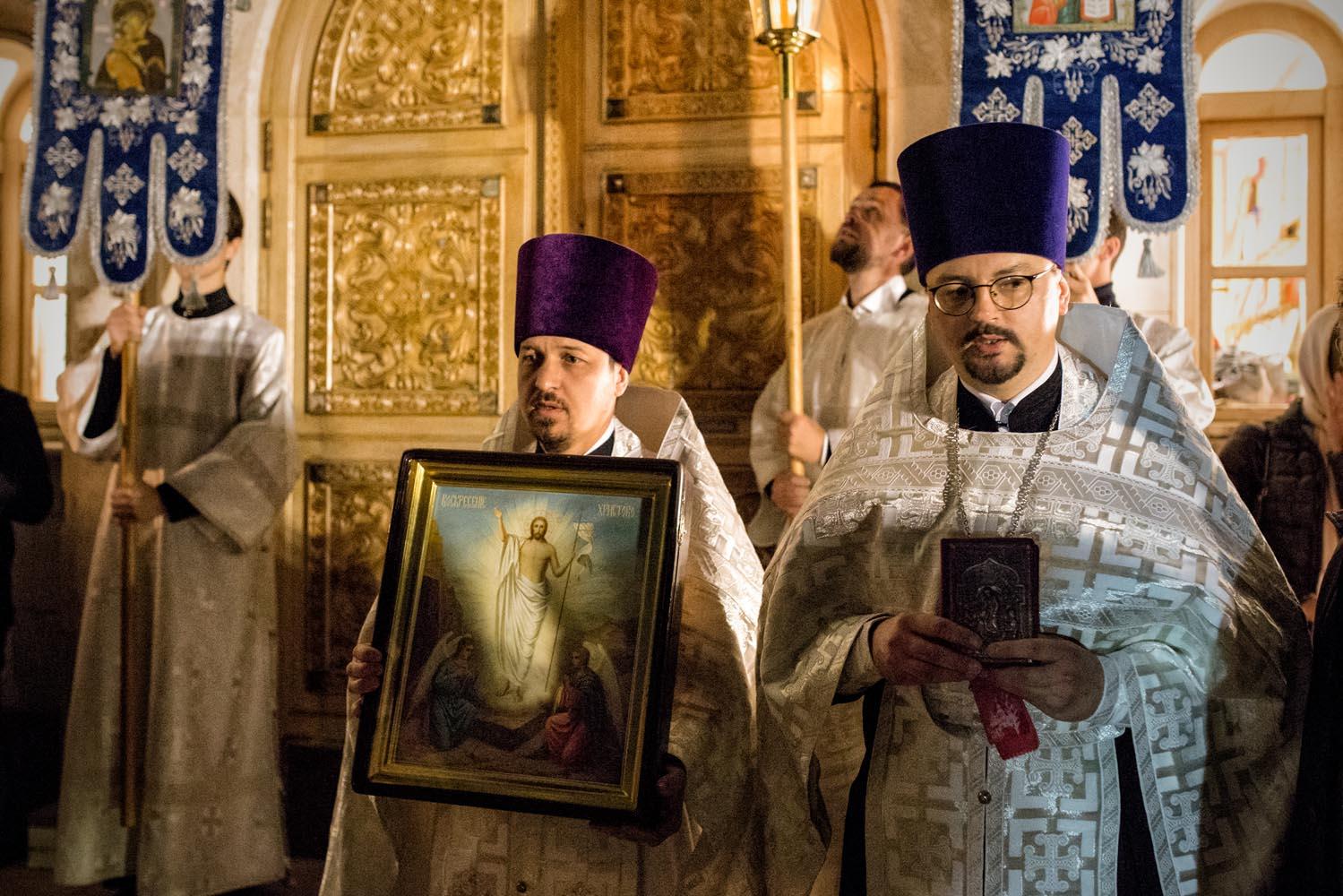 Rome, Italy, Apr 2018.  I presbiteri Alexis (a destra) ed Edvard (a sinistra) pregano di fronte all'ingresso della chiesa, subito prima dell'inizio dell'inizio della divina liturgia.
