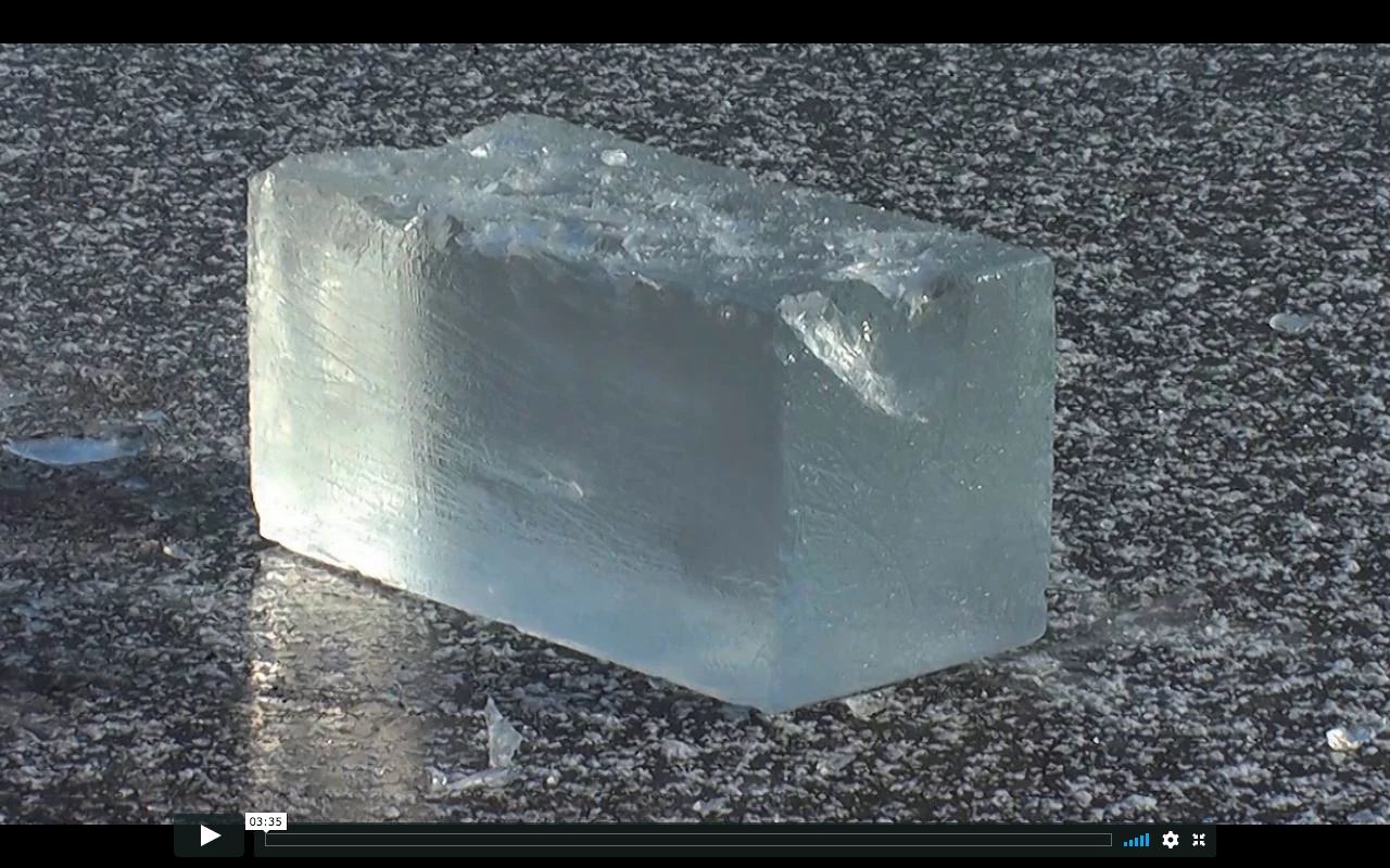 Still from video  Nothing is Destroyed , where a block of ice is chipped to fragments and reappears whole in an endless cycle.