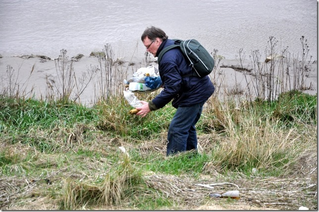 The artist collecting trash from beside the Great Ouse river for making into art as part of the Trash | Art show.