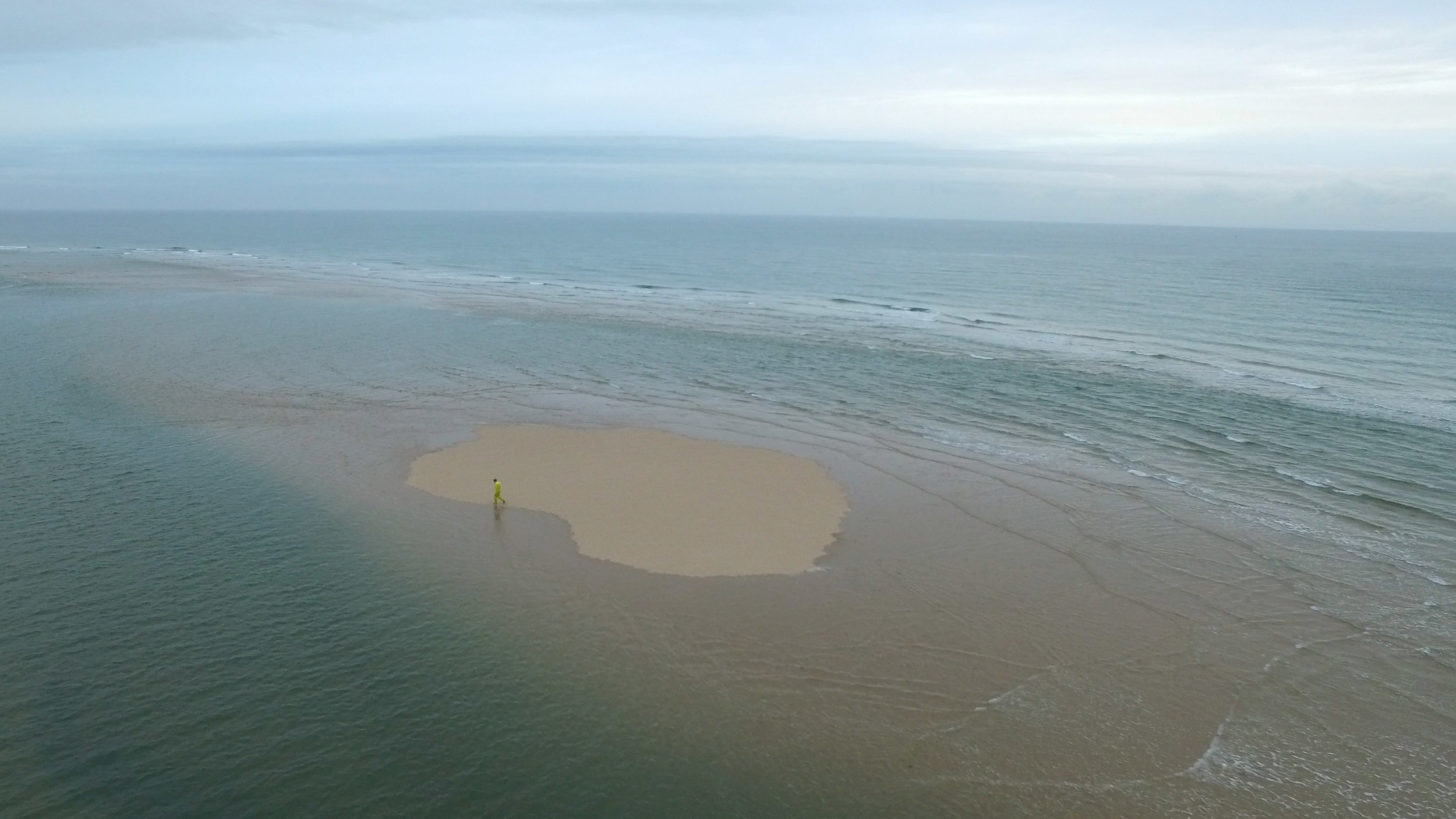 Simon Faithfull's film, 'Going Nowhere 1.5' shows a lone man in a yellow suit walking doggedly around an intertidal island. We see the figure walk around the decreasing space, as the sea expands around him, until the sea is all we see.