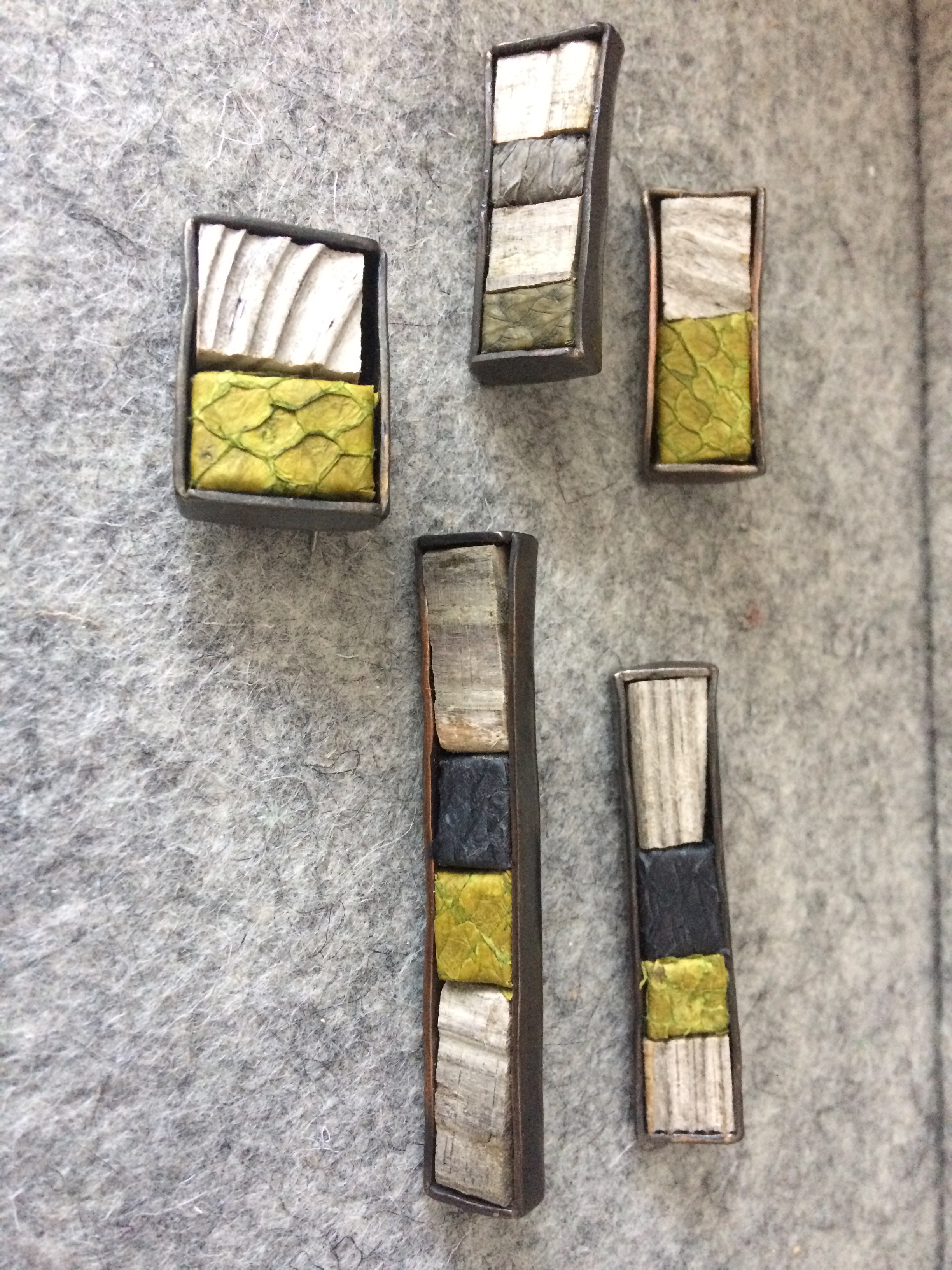 Helga Mogensen brooches (to be worn horizontally or vertically) made from driftwood and fish leather set in metal.
