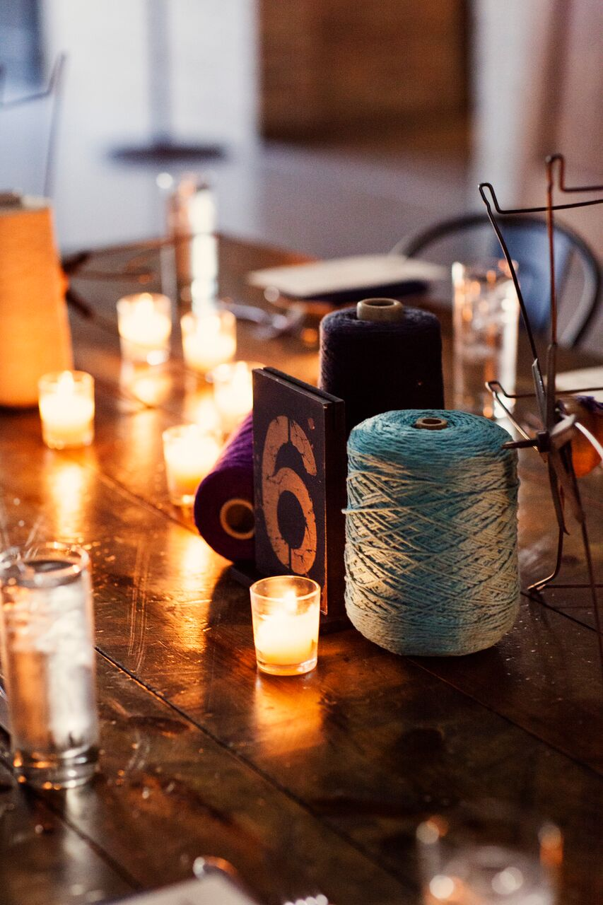 tea lights and votives surrounding distressed table number  Planning By Wrap It Up Parties  Artifact Events