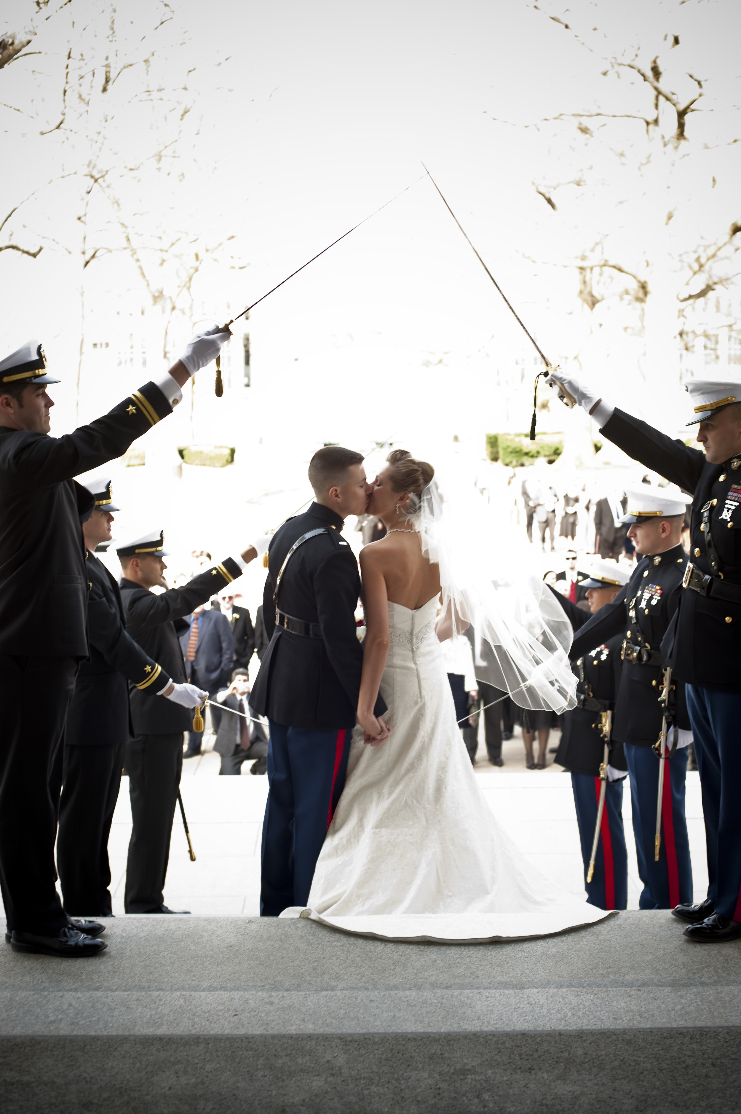 Couple kissing before entering sword arch