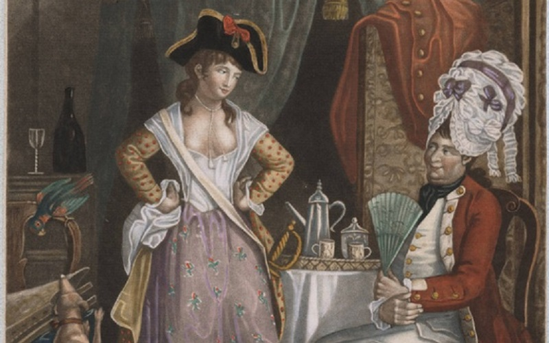 A bare-breasted woman wears a masculine hat, a man wears an elaborate feminine wig and holds a fan.