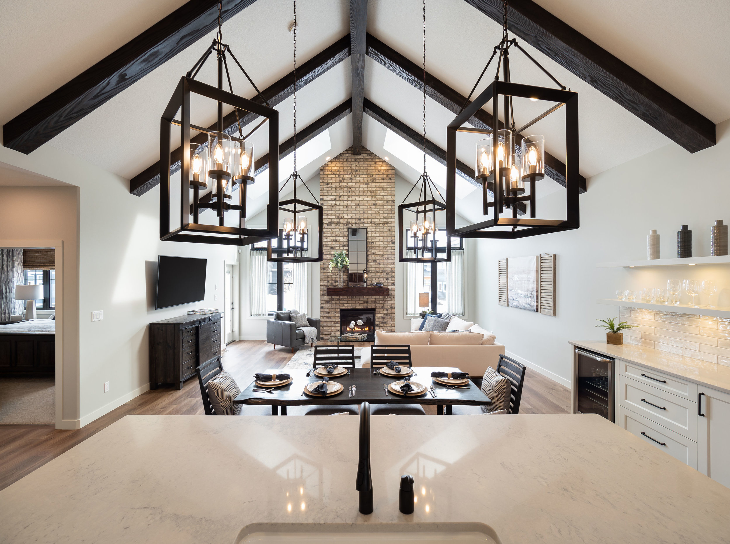 A floor to ceiling fireplace is the focus in the living room with large lantern lights in the kitchen balancing the room.