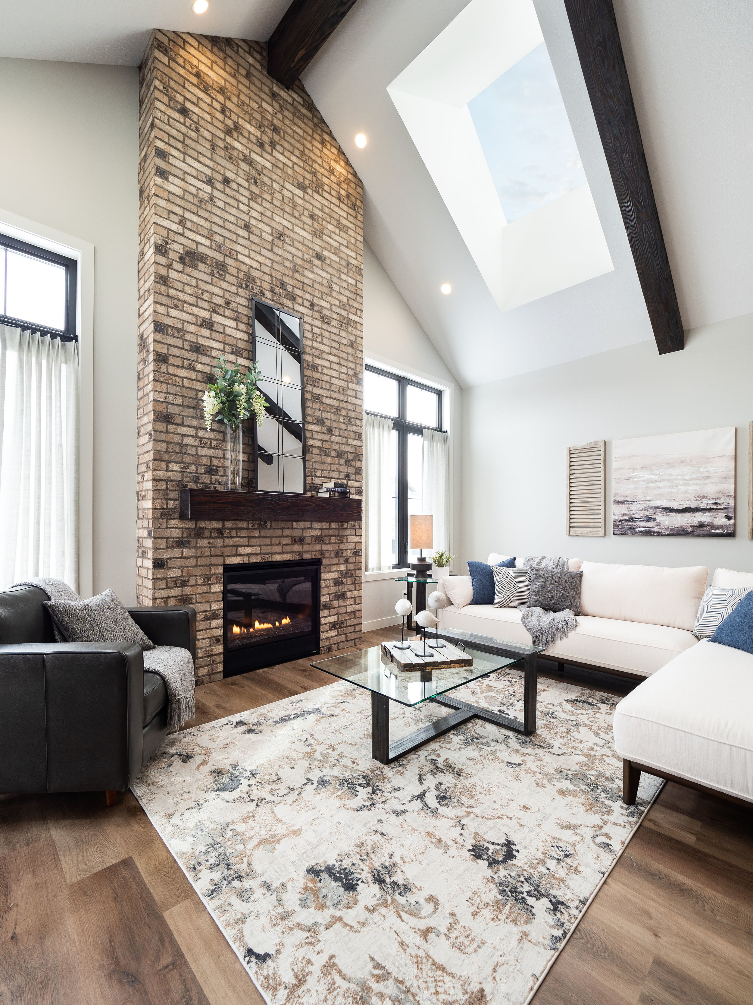 Staring back at you is a floor to ceiling fireplace that seamlessly blends into the vault above. The natural color of brick was the perfect match for the exposed beams which paired with the mantle perfectly.