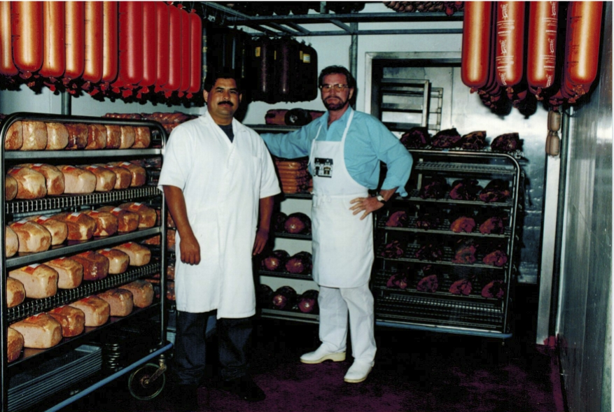 WURSTMACHER EUGEN GOETS (RIGHT) WITH SAM HERNANDEZ (LEFT) STANDING IN ONE OF CONTINENTAL'S DELICIOUSLY FILLED SAUSAGE WALK-IN COOLERS.
