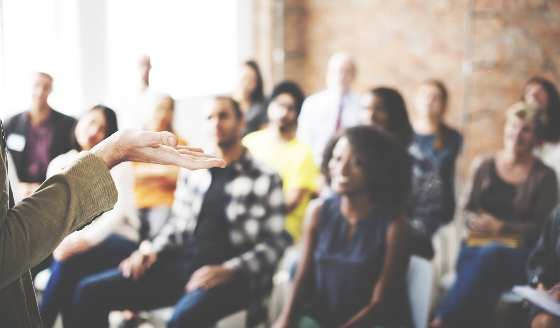 Woman speaking in front of diverse audience of adults