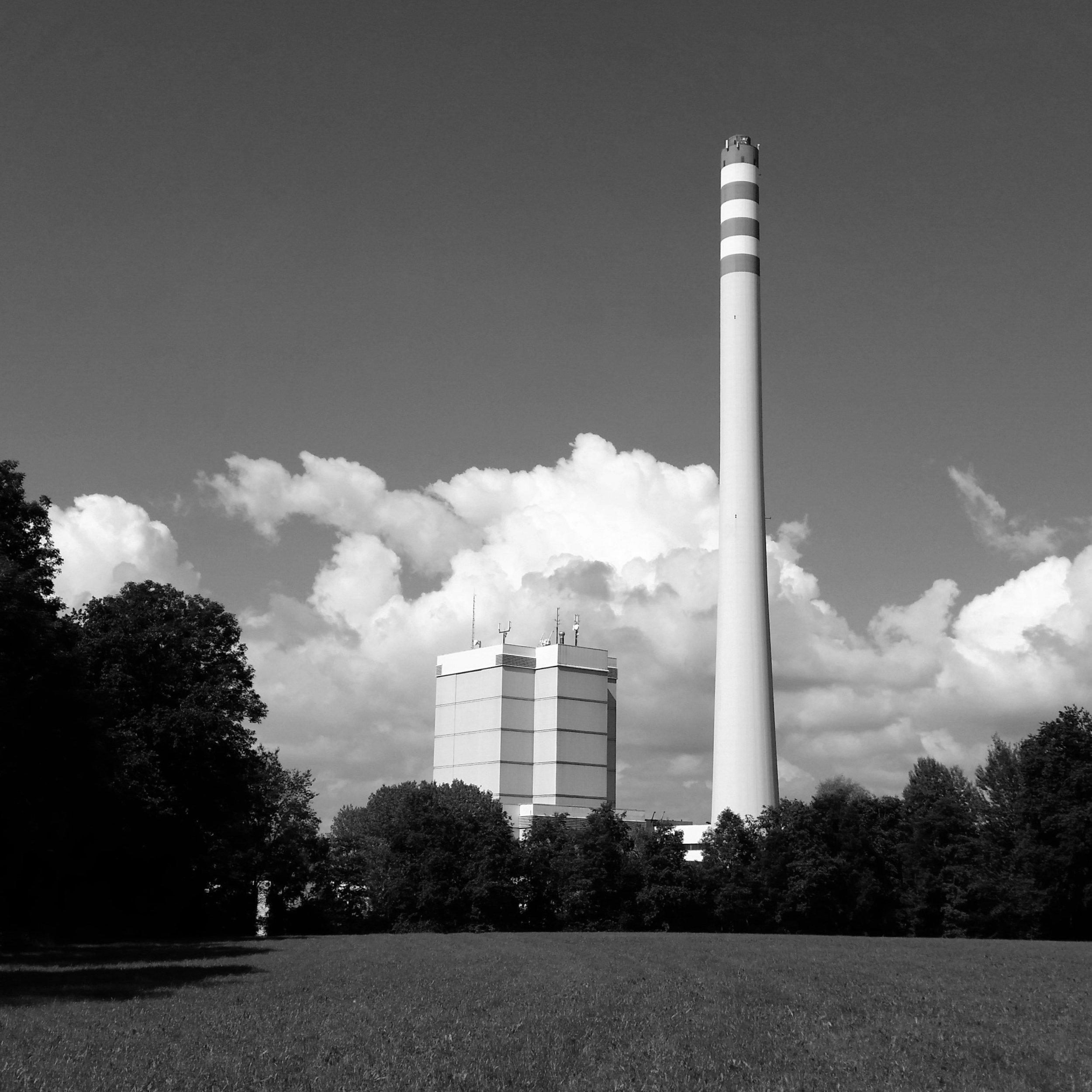 The black-and-white photograph shows a steam plant with a tall building and high smokestack at the end of a grassy field. The smokestack has stripes at its top, almost like a lighthouse. Clouds appear on the horizon.