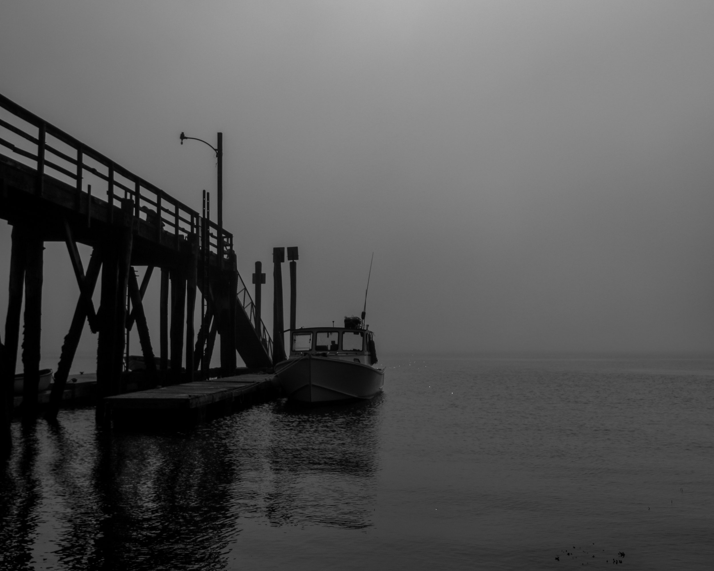 Image depicts a black and white photograph of a fishing boat docked at a pier. The tide is low, so the pier stands much higher than the level of the water. The photo seems to be taken from shore, and low contrast in the photo creates a gloomy, gray atmosphere.