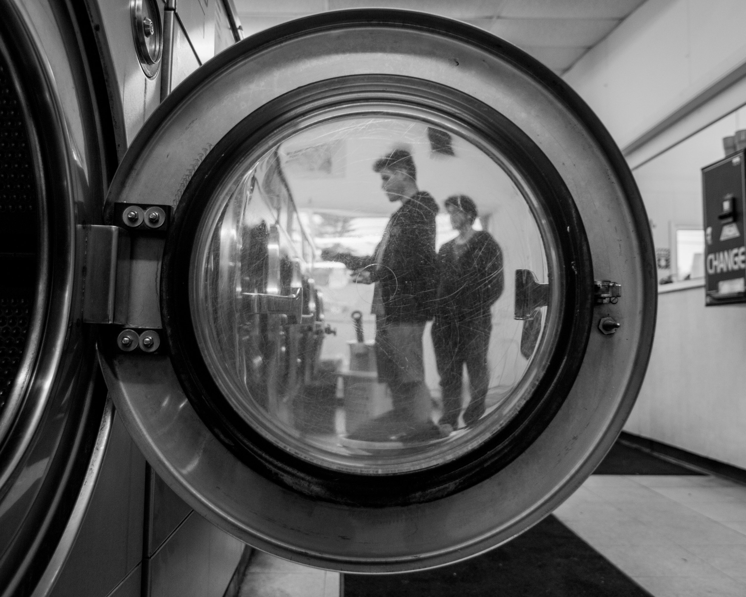 In the black and white photograph, two figures, who appear to be young men, are framed by an open washing machine door. The door is mostly transparent, though it does blur the figures slightly. The photograph is taken low to the ground, facing down the line of washing machines in a laundromat. One figure seems to be about to put money into the machine, and the other person stands behind.