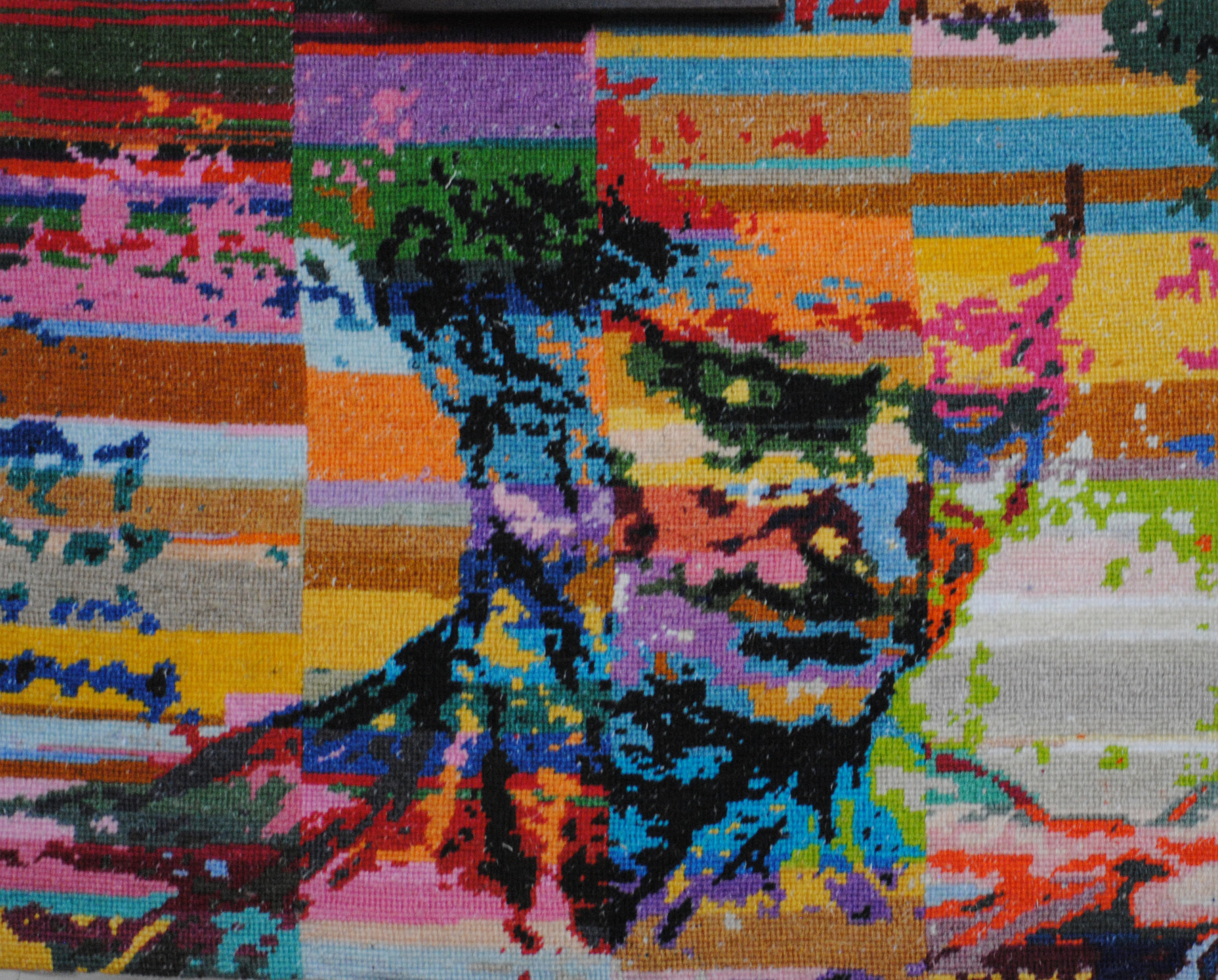 Holly Day's needlepoint is a rendering of one of Leonardo de Vinci's sketches. It depicts the down-facing head and shoulders of a man in da Vinci's life-like style. In the embroidery, the figure appears against a background of of small, asymmetrical blocks of bright color. The figure is stitched in colors that contrast with the background block, giving the sketch a dynamic feel.