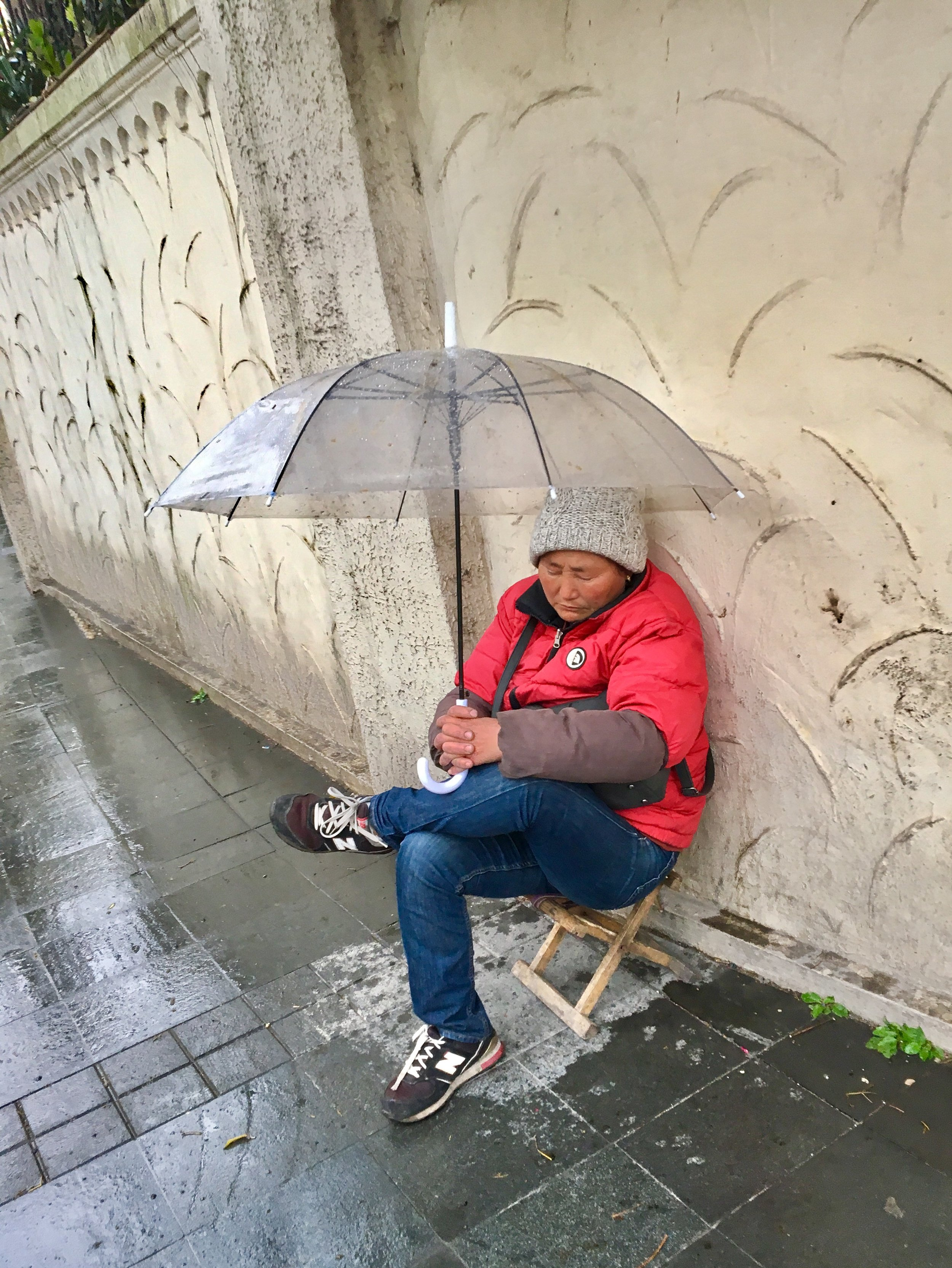 Flower Vendor Takes an Afternoon Nap in the Cold of Winter