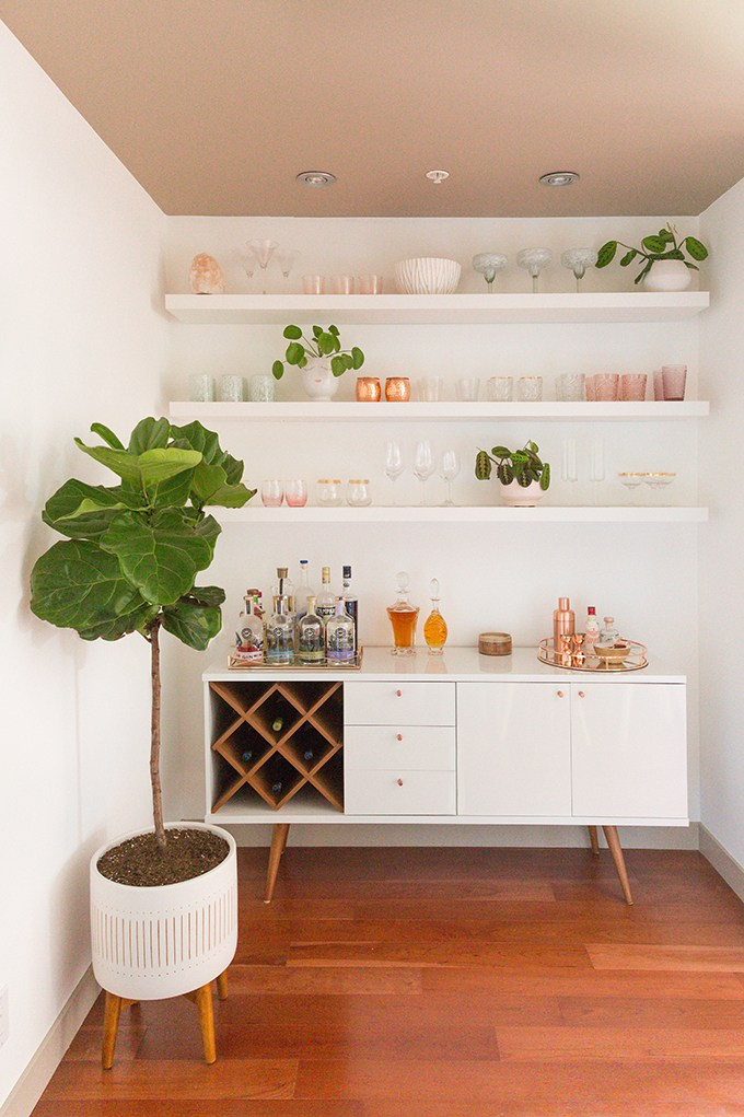 Courtesy JustineCelina.  A dead corner turned into a pretty bar area. Simple floating shelves and a cabinet on fifties-style legs and you are good to go!