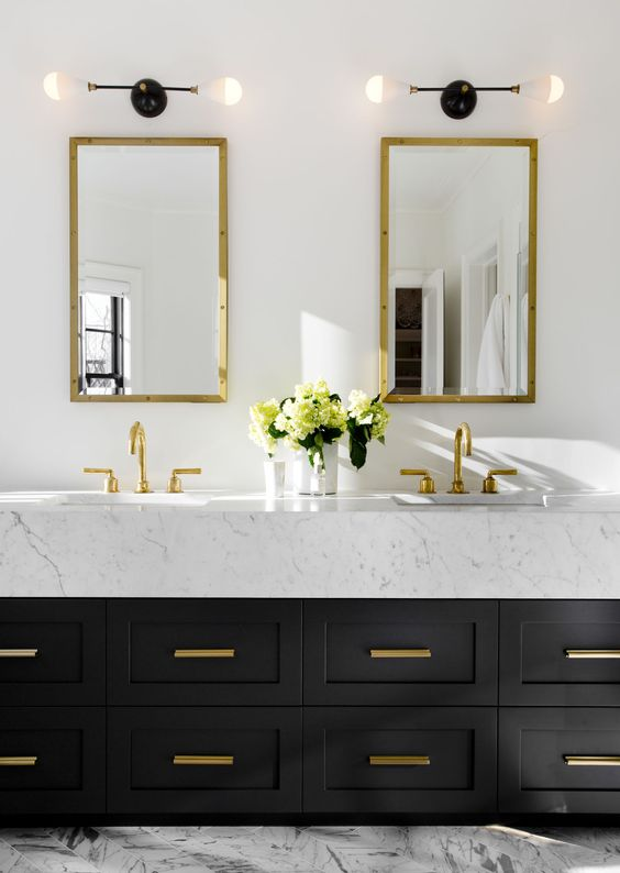 The brass hardware, mirrors and faucets work beautifully together with the black of the vanity and the white marble countertop. Source: Unknown.