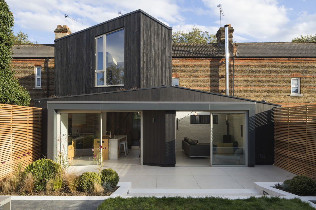 A row house extension in London (UK) by Neil Dusheiko whose firm regularly designs additions. Note the contrast between the old brick of the existing house, the black addition and the clean lines of the garden layout. This addition allows for a modern kitchen and sitting area as well as an extra room on the first floor. Artfully done.