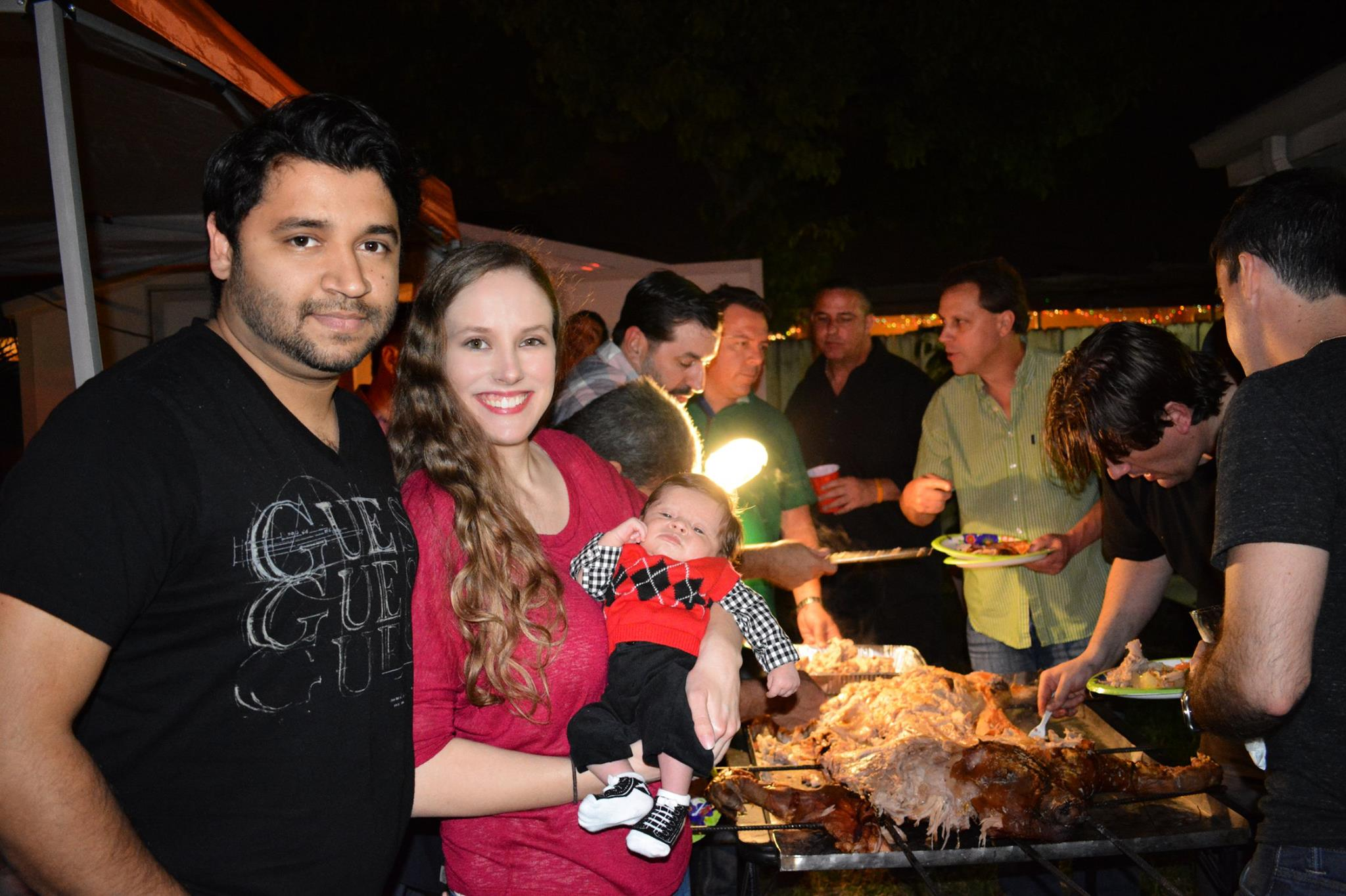 Noah at his first annual pig roast (almost 1 month old!), with Tio Ray carving el puerco in the background and Cousin Louie holding up the lamp.