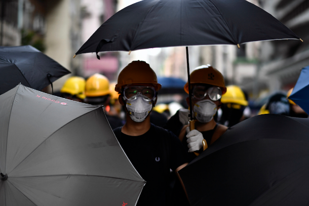 Pro-democracy protesters stand together with umbrellas as they face off with police during a demonstration in Hong Kong on July 28. (Photo by Anthony Wallace/AFP)