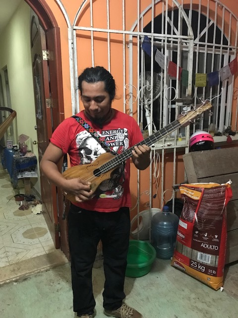 A talented local musician we met through our local friend, who played some of his instruments for us while we were at his house. He made the guitar and the one my friend is pictured holding.