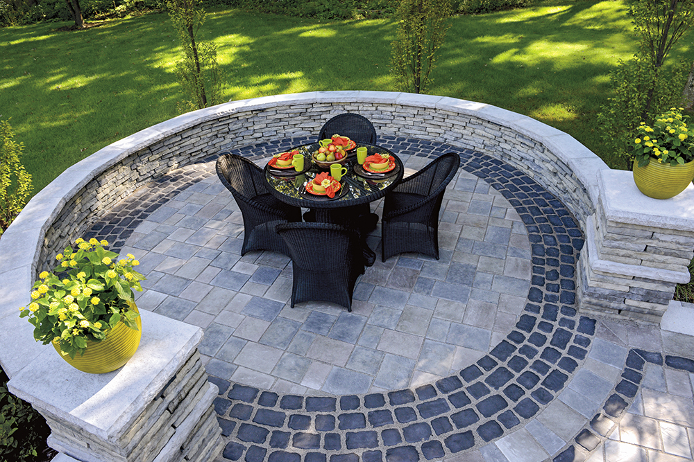 RICHCLIFF PATIO IN DAWN MIST AND PEBBLE TAUPE WITH COURTSTONE ACCENT IN BASALT, RIVERCREST WALL IN COASTAL SLATE WITH LEDGESTONE COPING AND PILLAR CAP IN GREY