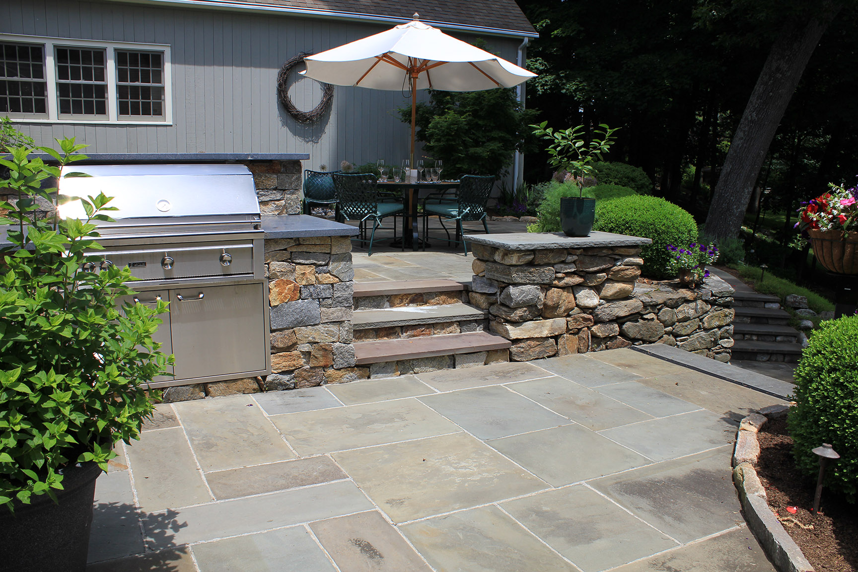 MATERIALS USED: FULL RANGE, NATURAL CLEFT BLUESTONE PATIO; CT FIELDSTONE WALLS; CT FIELDSTONE LEDGE CUT AROUND GRILL WITH NEWPORT DARK GRANITE COUNTER