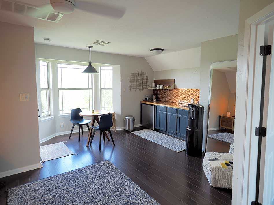 Apartment kitchenette includes a small fridge, water cooler, and sink