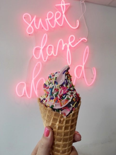 Fruity Pebble and Black Velvet soft serve with sprinkles on a waffle cone.
