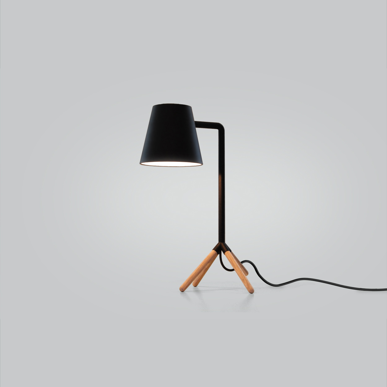 Slightly Awkward Lamp   Exhibition: CITE Goes America 2010  The defining beauty in people is often the characteristic that doesn't fit the standard mold. The Slightly Awkward Desk Lamp was simple and minimal, but with a peculiar posture. The awkward stance of the lamp, with its truncated fourth leg, gave it life and personality while allowing it to balance as an ambient table lamp or a directional task lamp.