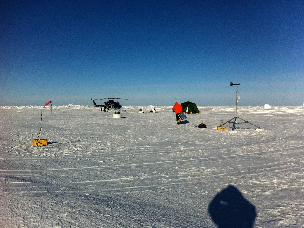 Springtime deployment of an instruments cluster: (L to R) Ice Mass Balance Buoy, Wave Buoy (with two additional instruments lying on the ice near the helicopter) and an Autonomous Weather Station.