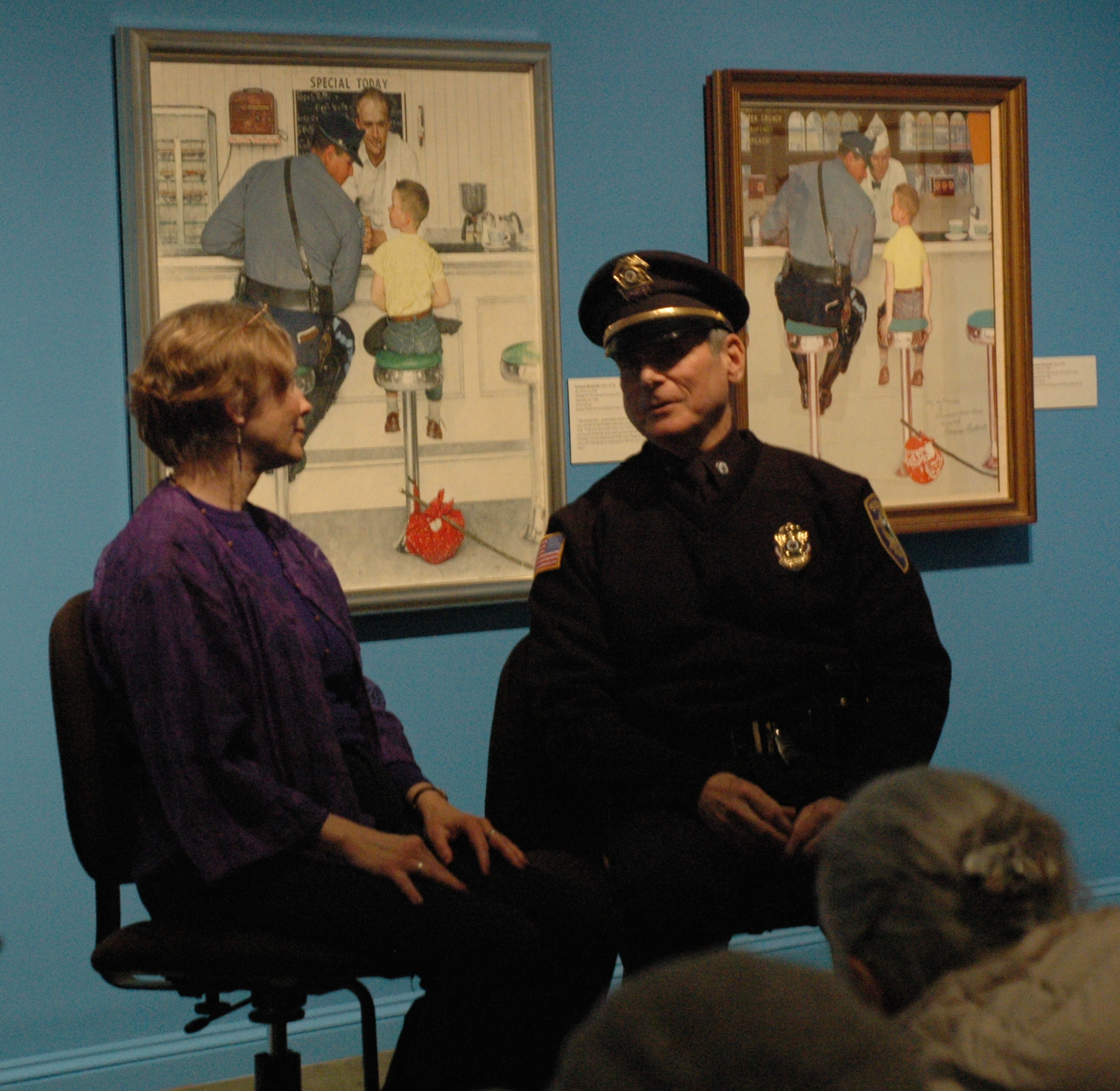 "Natalie Shiras, Pastor at Church on the Hill in Lenox, MA and Police Chief of Stockbridge, Rick Wilcox in  ""Trust,"" seated by the ""Runaway"" painting by Rockwell"