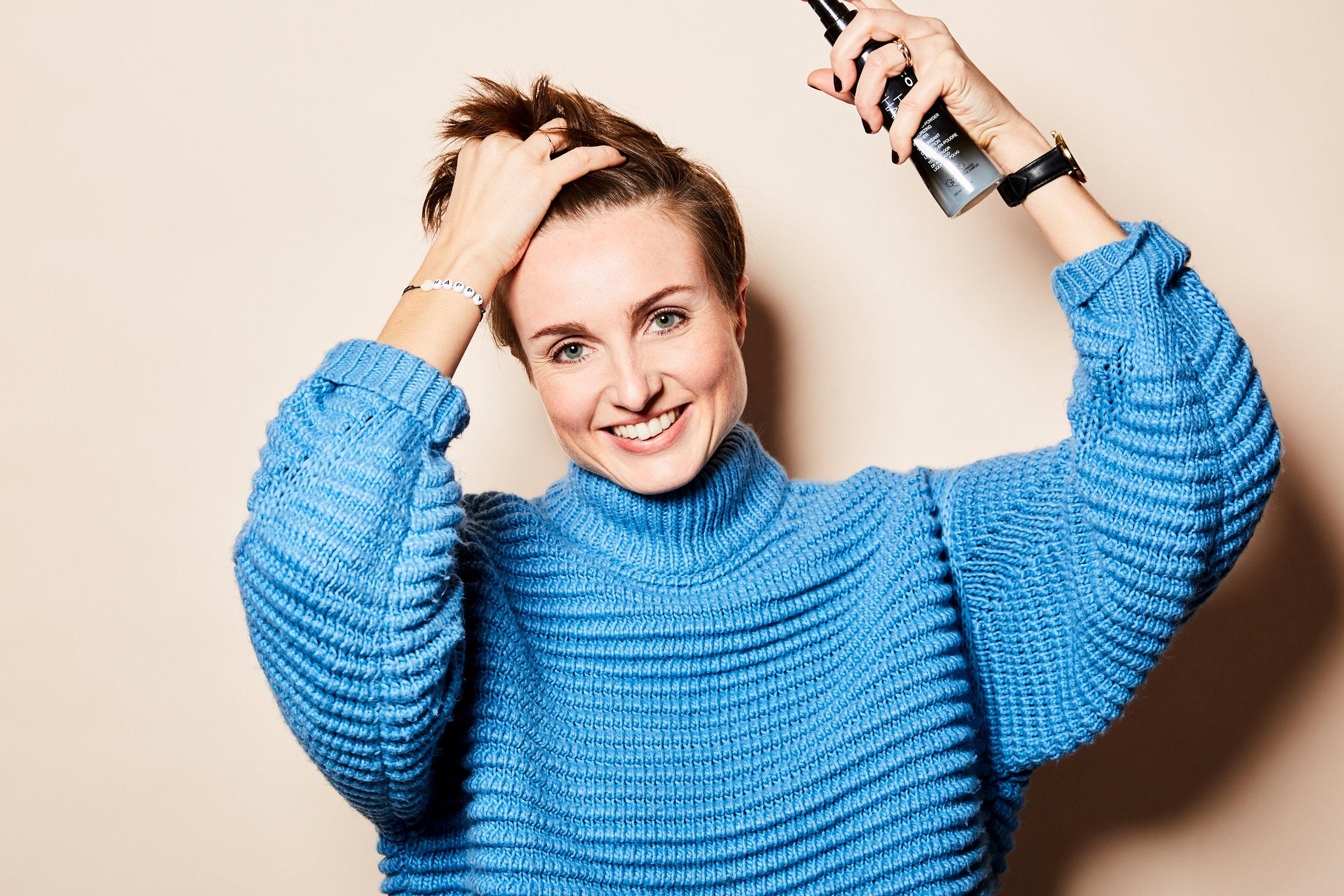 Juli sprayt den Hair Shaker von Joico an ihre Ansätze und knetet das Produkt gut in die Haare ein.