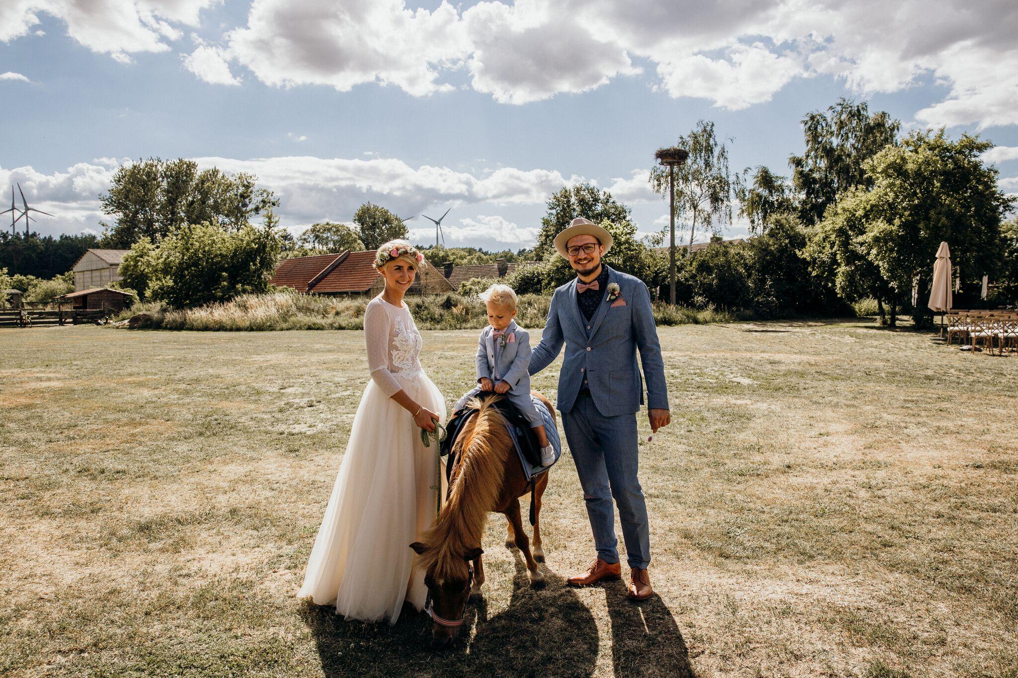 Familie Kölsch mit Pony Susi. Roses Kleid ist von  Mia Lavi,  wird noch ein großes Thema in Teil 2.Der Anzug von Sohn Jasper ist von  h&m und das Einstecktuch und Fliege haben sie passend zu Papa nachnähen lassen. Roberts Anzug ist von  Just for Boys  und der Hut von  Hut Styler.