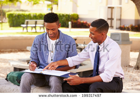 stock-photo-teacher-sitting-outdoors-helping-male-student-with-work-199317497.jpg