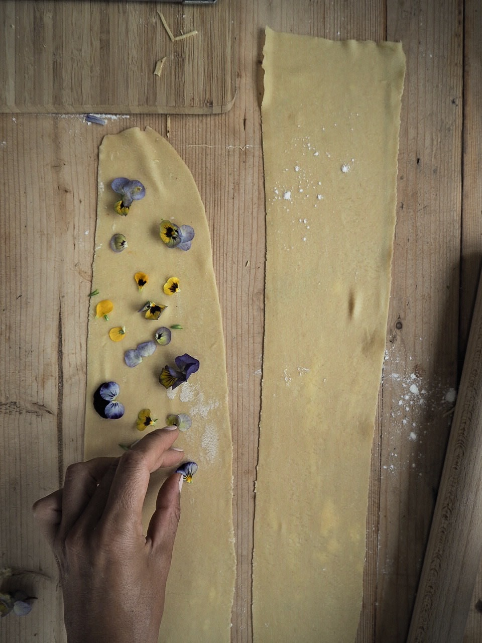 Edible flowers being laid out on top of homemade fresh pasta