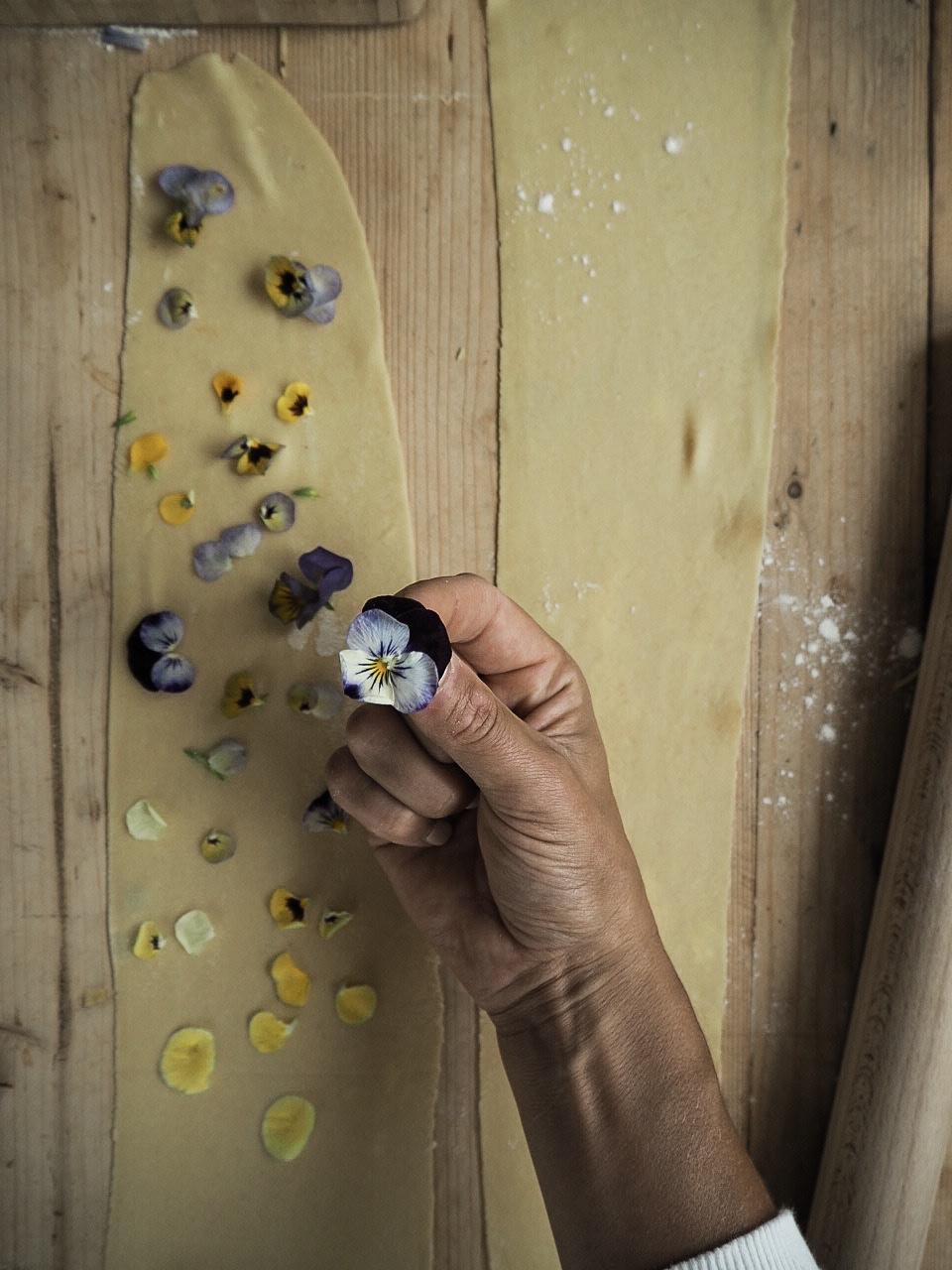 Laying out edible flowers over fresh pasta before pressing