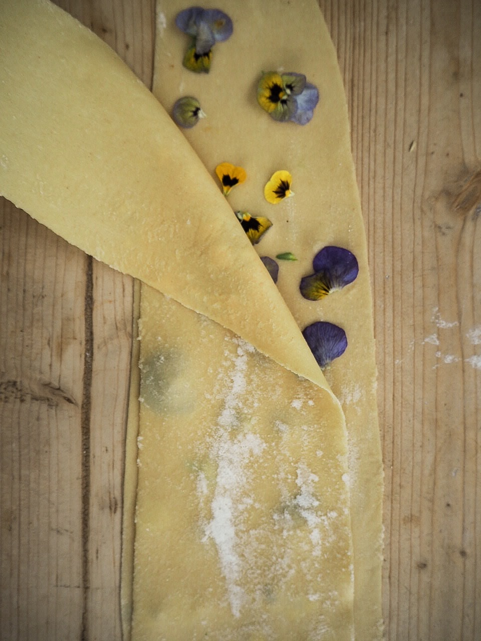 laying fresh pasta over the top of edible flowers before pressing