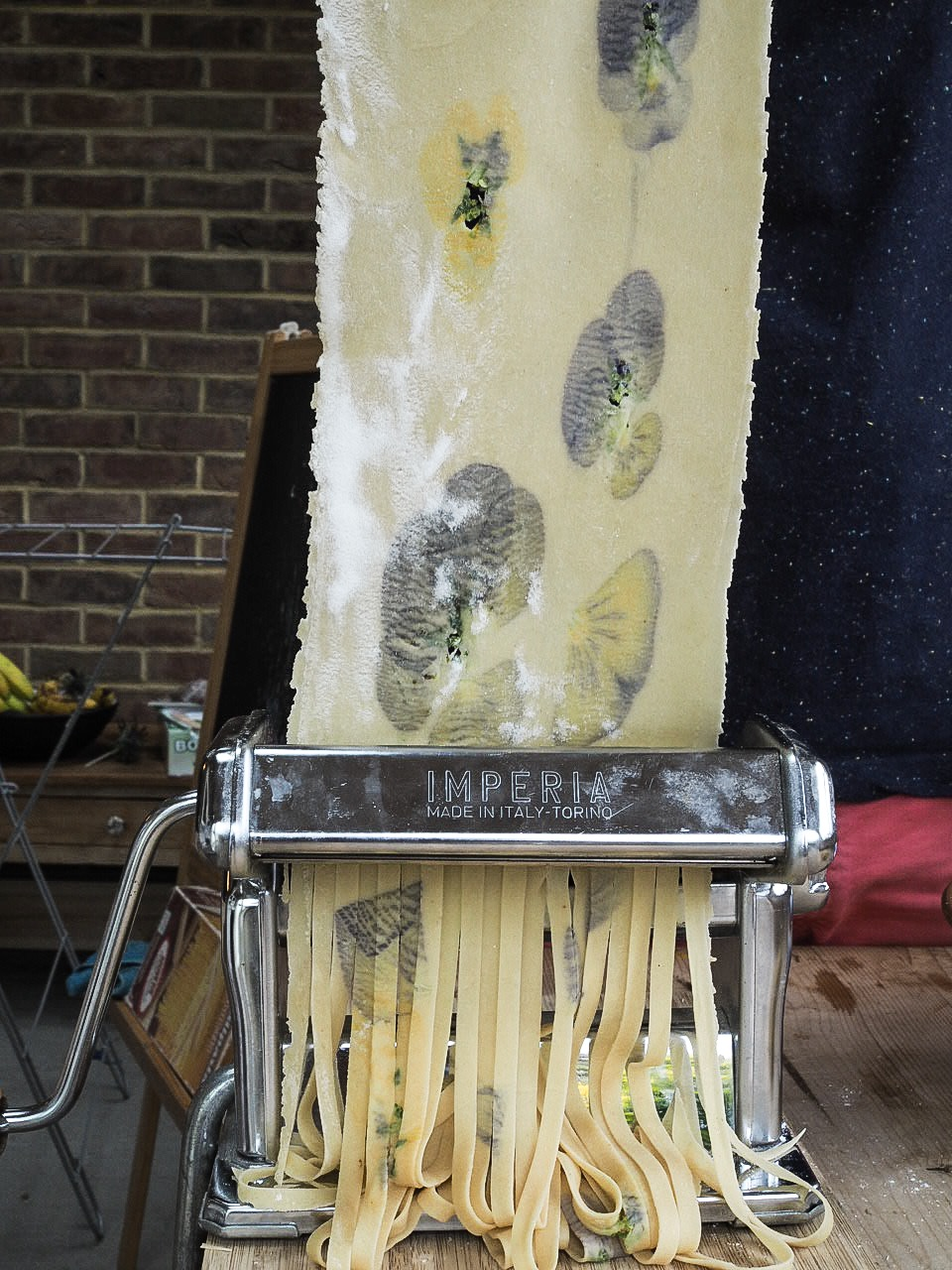 fresh pasta with edible flowers being cut into tagliatelle