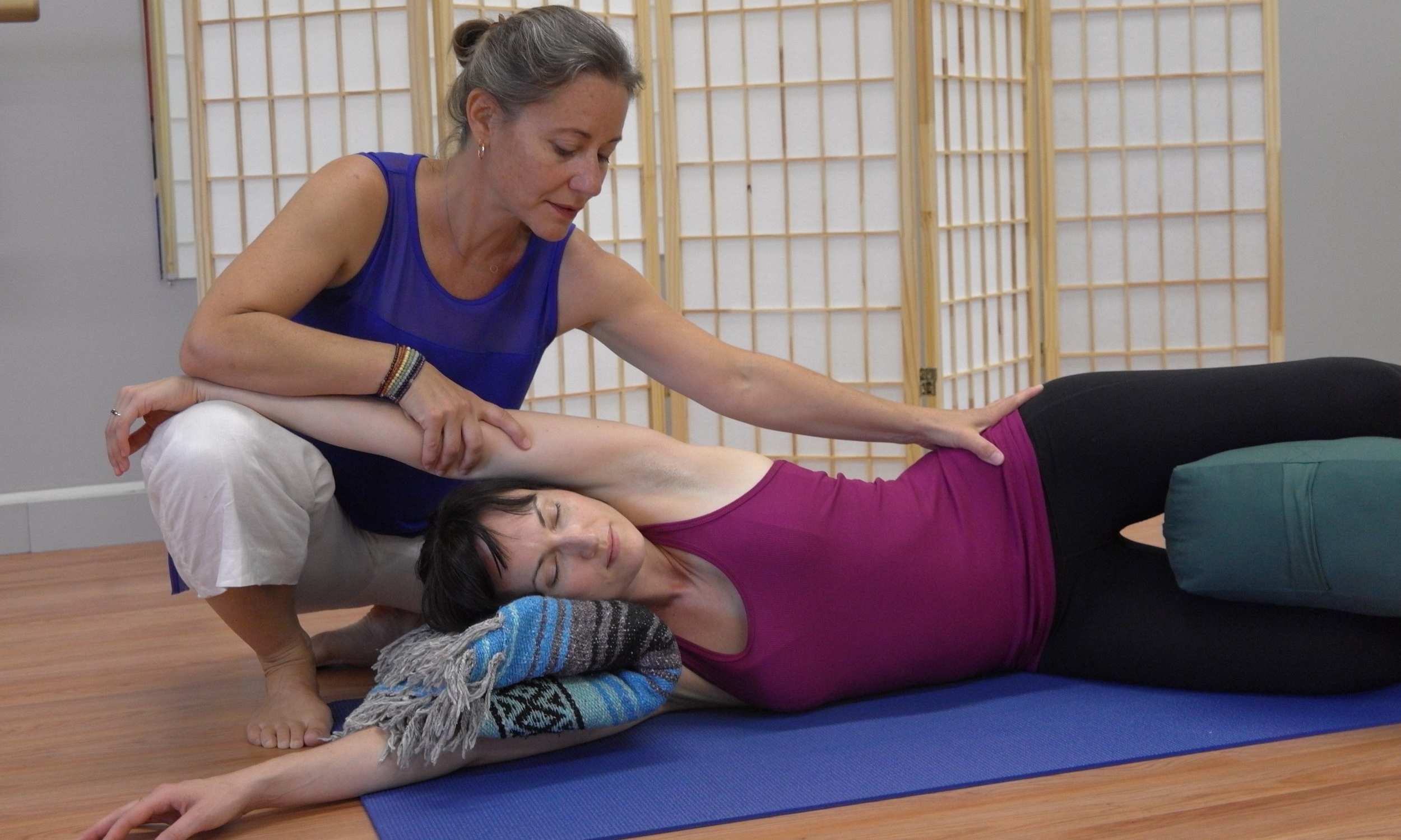 Phoenix Rising Yoga Therapist, Lucy D'Aponte, assisting a posture.