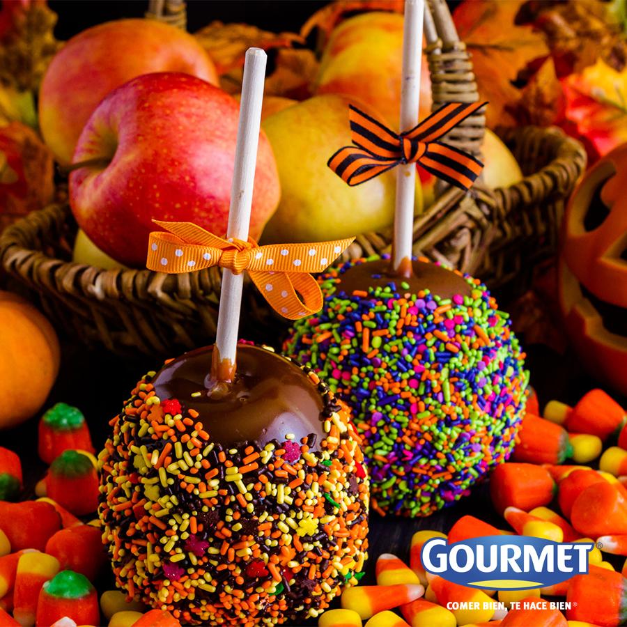 Manzanas arcoíris - Sumérgelas en chocolate derretido al baño María. Cuando las retires, agrega grajeas de colores para decorarlas.