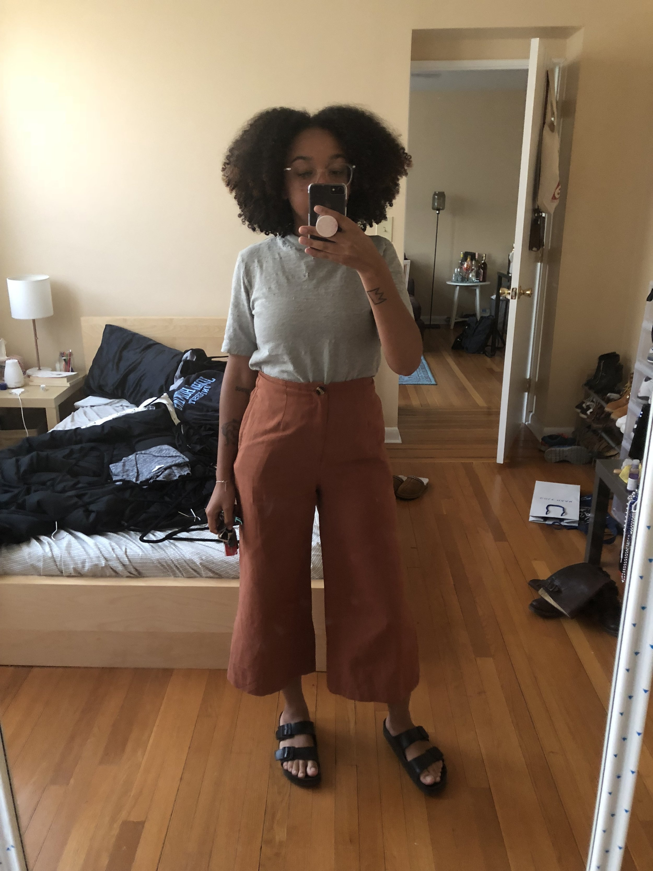 Image description: Allison is standing in a mirror. They are holding a black iPhone. They are wearing a gray top, orange pants, and black shoes. There is a bed, nightstand and door behind them.