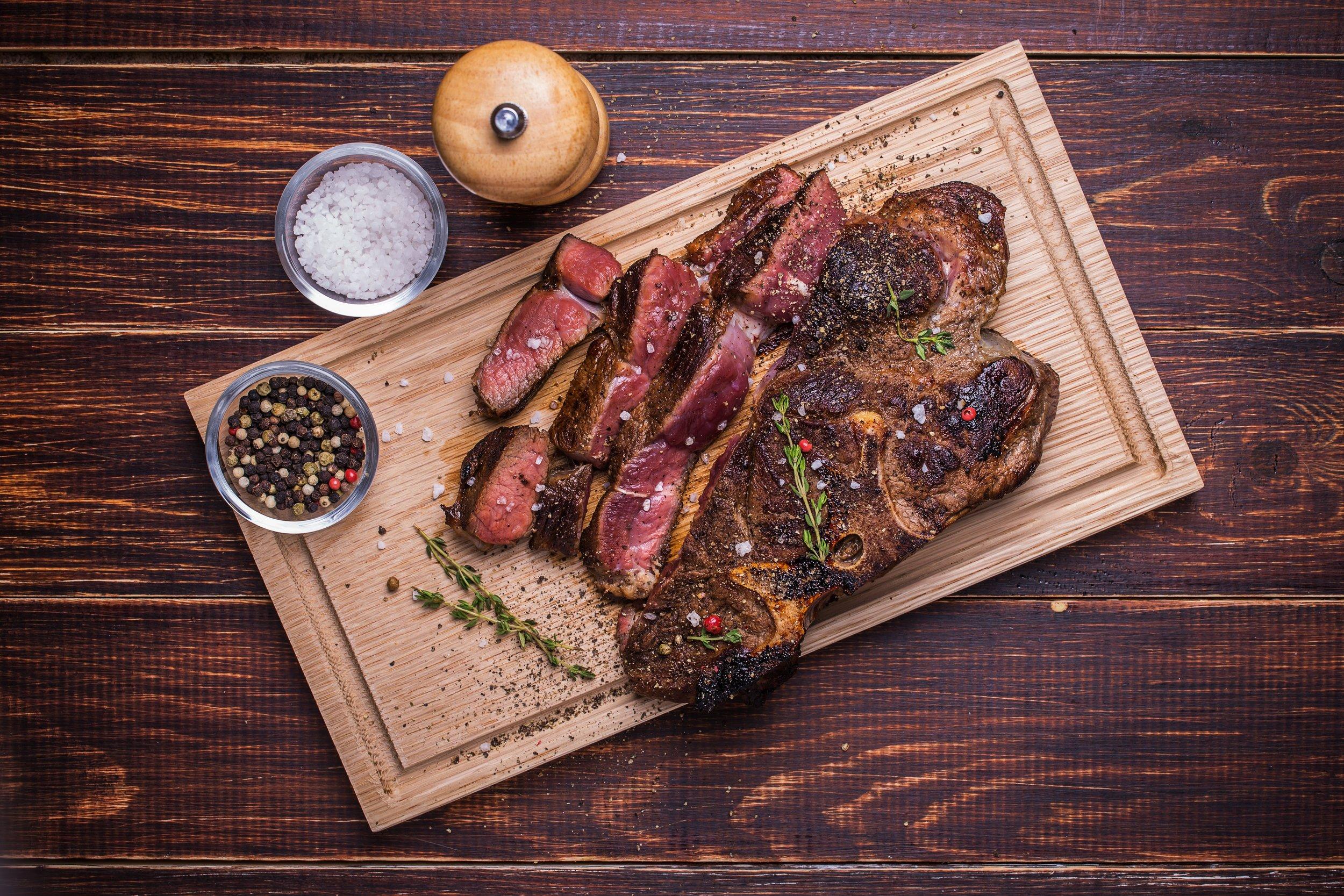 Beef steak on a wooden background.jpg