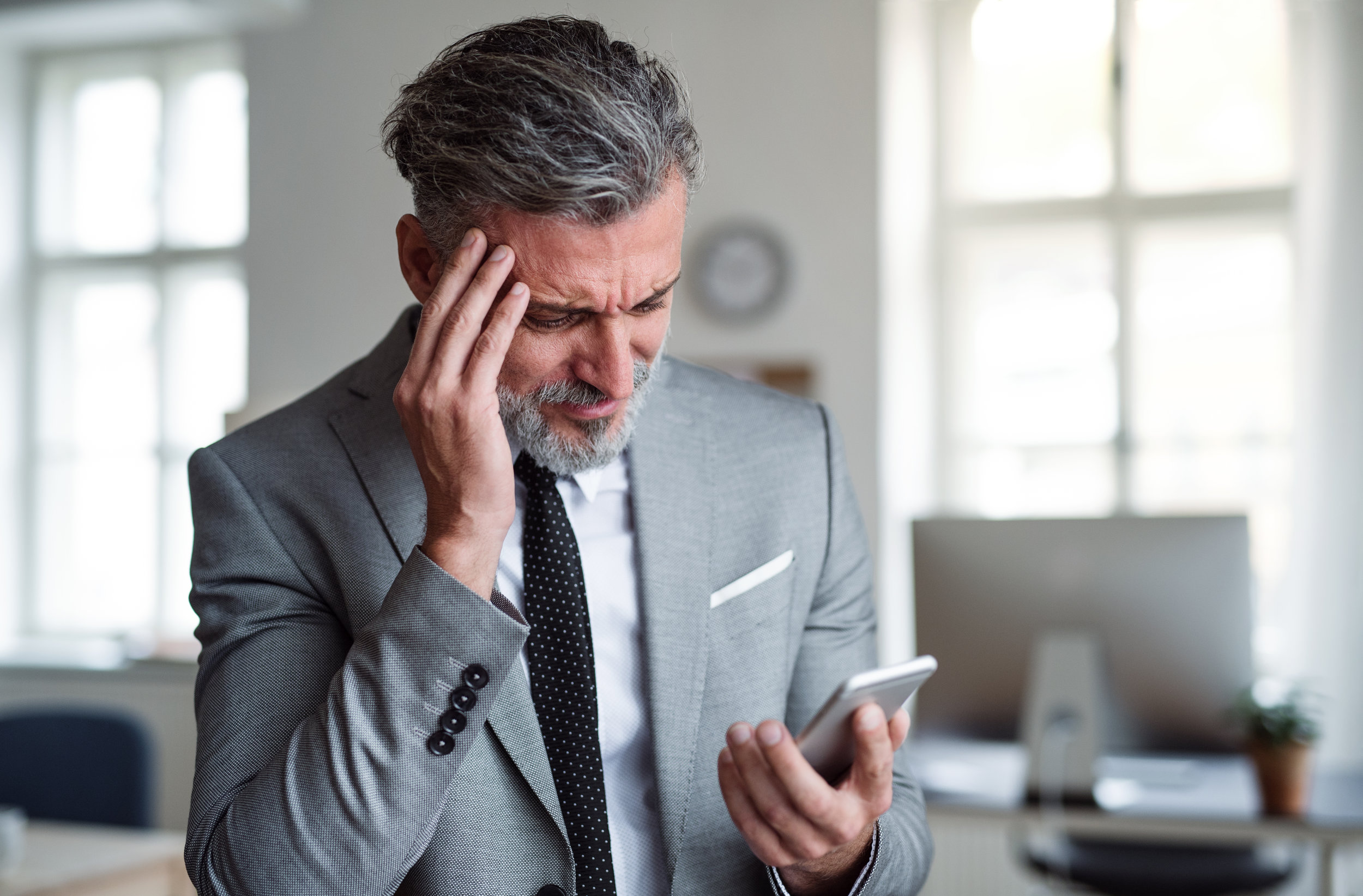 A frustrated businessman with smartphone standing in an office, reading bad news.