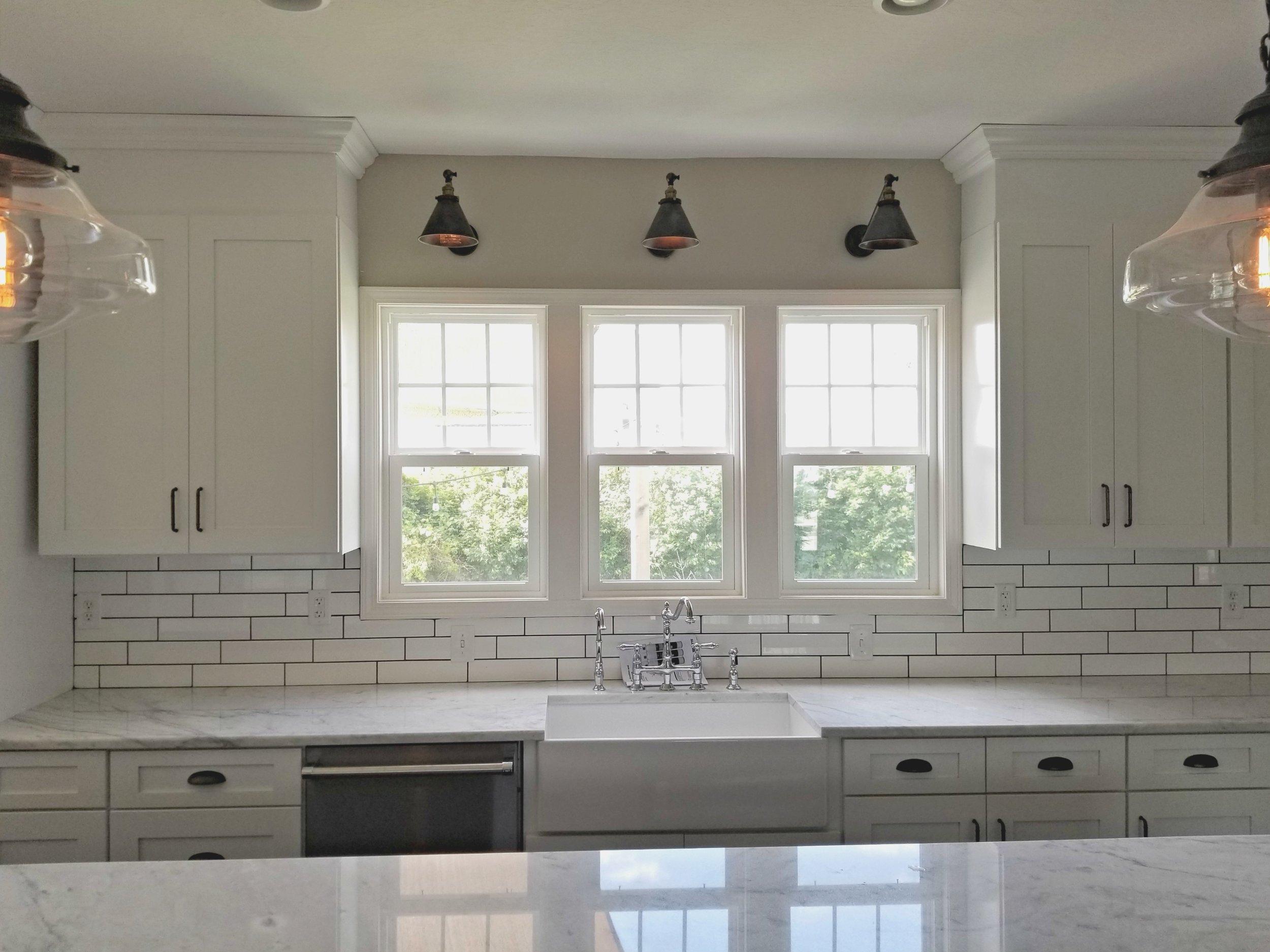 - Subway tile backsplashFarm-style sinkCustom cabinetsNew windows cut into wall for natural light
