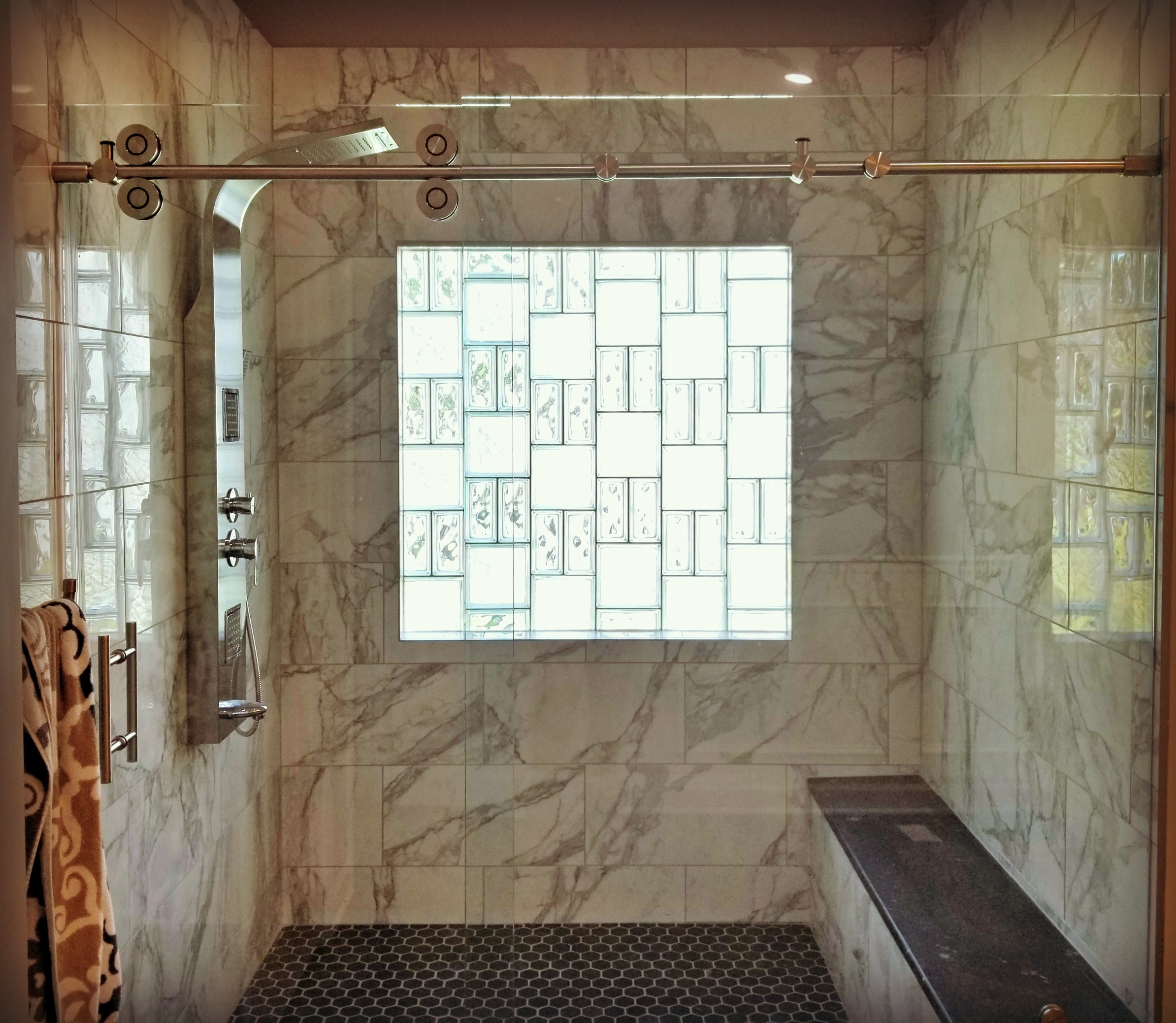 - Marble tile in showercustom glass block windowBrushed nickel shower towerCustom sliding shower glass door