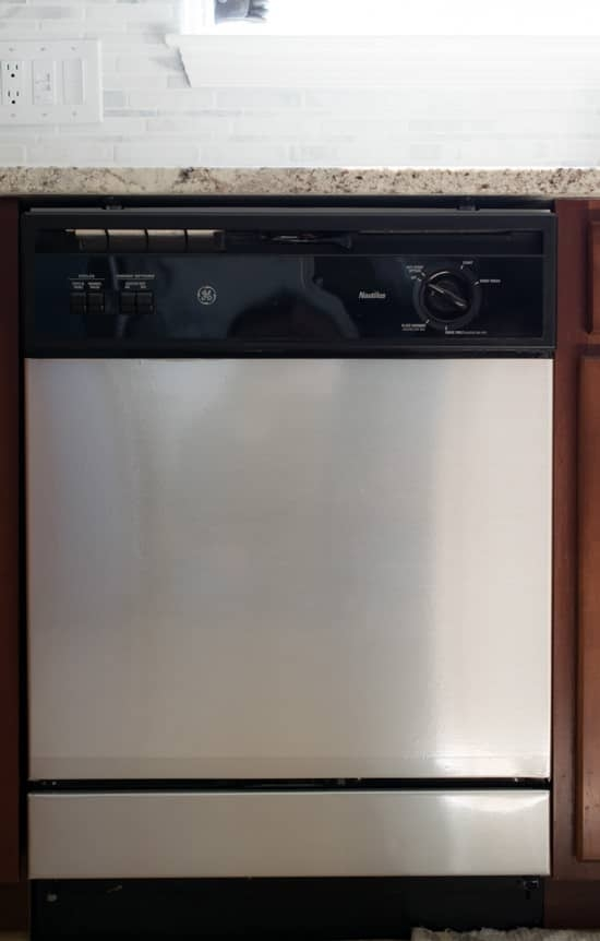 Follow the link provided in our text to find out how $10 of faux metal contact paper can turn a tired old dishwasher into this beauty.